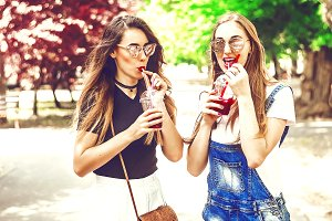 two girls are drinking a cocktail. ice cubes in a drink. sunglasses and long hair. communication on the street. summer
