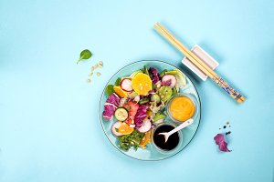Fresh salad with fruits and greens on blue background
