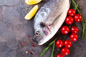 Fresh uncooked dorado or sea bream fish with lemon slices, spices, herbs and vegetables.