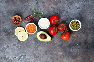 Fresh vegetables ingredients for salad with mung beans, rice, lentils on stone background, top view,