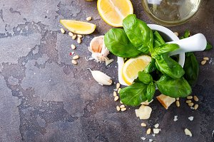 Ingredients for making pesto sauce on a stone background,