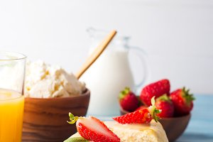 slice of strawberry cheesecake on white blue background with milk and juice