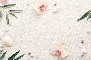 Seashells, flowers & pearls on sand