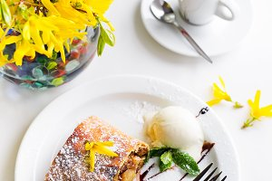 Apple strudel with vanilla ice cream and coffee, yellow flowers