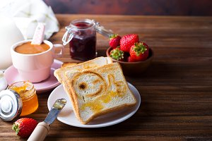 Toast with a smile, jam, coffee and fresh strawberries for breakfast