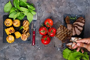 female hand holds a fork with steak on the background fresh three types of grilled steak on slate plate with spinach, tomato and grilled potatoes