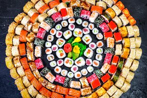 close up of a variety of sushi rolls in different colors and flavors