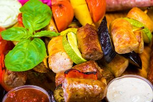 hot browned ruddy homemade sausages on a wooden tray with sauces and vegetables