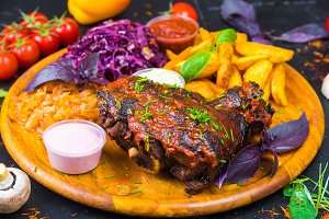 Ruddy, roasted knuckle on a wooden Board with vegetables, sauce and fresh herbs