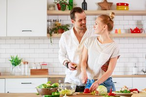 Photo of young couple in love preparing breakfast in kitchen