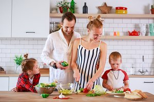 Image of young mother and father with son and daughter preparing breakfast