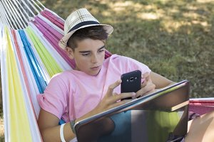child in hammock with computer and mobile phone