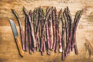 Fresh purple asparagus over wooden background