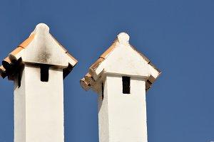 Two white chimneys on blue sky