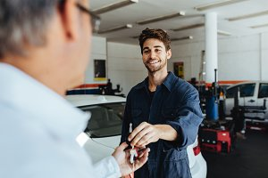 Mechanic giving car keys to customer