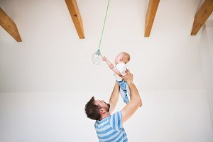 Young father holding a baby son under the ceiling at home.