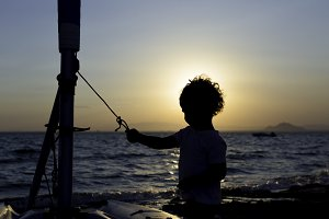 backlight of a kid on the beach