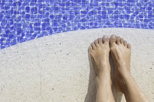 feet of a woman on the edge of  pool