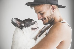 Tattoed boy with French Bulldog dog on white background
