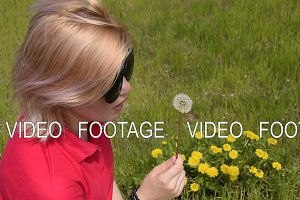 Beautiful blond girl blowing dandelion.