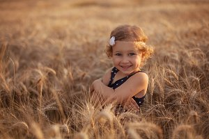 Smiling little girl on a wheat field