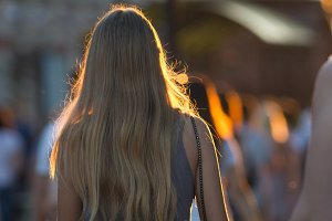 Rear view of young caucasian woman walking in crowd on the pedestrian street at summer sunset
