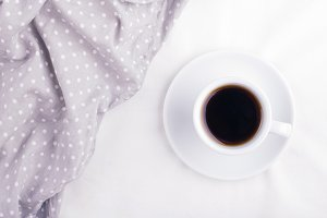 The cup of coffee on the bed.