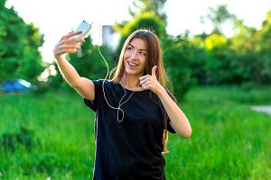 Young brunette woman smiling happily in summer in the park. Communicates in social networks. Hands gestures with a thumbs-up. Emotional communication in a video call. In a black T-shirt.