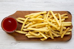 French fries with sauce on wooden