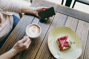Close up of top woman sitting in coffee shop with cup of cappuccino, cake, relaxing in restaurant during free time. Female holding mobile phone with blank empty screen, rest in cafe. Lifestyle concept