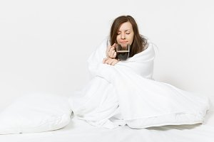 Young tired brunette woman sitting in bed with cup of coffee, white sheet, pillow, wrapping in blanket on white background. Female spending time in room. Rest, relax, good mood concept. Copy space.