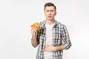 Illness sad young man in shirt put hand on pain abdomen, stomach-ache, standing and holding burger isolated on white background. Proper nutrition or American classic fast food. Area with copy space.