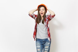 Young shocked beautiful woman in protective construction orange helmet clinging to head and screaming isolated on white background. Instruments for renovation apartment room. Repair home concept.