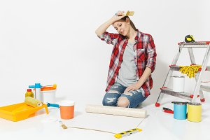 Woman in casual clothes sitting on floor with wallpaper rolls, brush, instruments for renovation apartment isolated on white background. Accessories for gluing, painting tools. Repair home concept.