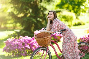 Portrait of trendy young woman in long pink floral dress stop to riding on vintage bike with basket for purchases on flowers background outdoors. Pretty female recreation time in spring or summer park
