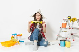 Woman in newspaper hat sitting on floor with building bubble spirit level, instruments for renovation apartment isolated on white background. Wallpaper, gluing accessories, tools. Repair home concept.