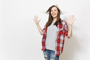 Young overjoyed beautiful woman in newspaper hat spreading hands with copy space isolated on white background. Accessories for renovation apartment room. Repair home concept. Advertising area.