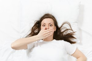 Top view of head of tired brunette young woman lying in bed with white sheet, pillow, blanket. Shocked female cover mouth with hand, spending time in room. Rest, relax, good mood concept. Copy space.