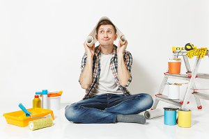 Fun young male sitting on floor with roll of wallpaper above head, instruments for renovation apartment room isolated on white background. Gluing accessories, painting tools. Repair home concept.