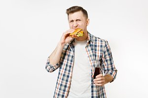 Handsome hungry young man in casual shirt holding and eating burger, cola in glass bottle isolated on white background. Proper nutrition or American classic fast food. Advertising area with copy space