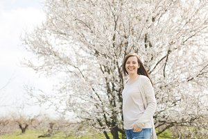 Young happy smiling beautiful woman in light casual clothes keeping hands in pockets standing in city garden or park on blooming tree background. Spring nature, flowers. Lifestyle, leisure concept.