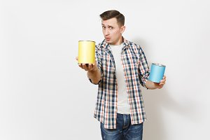 Young concerned handsome man in casual clothes pointing empty paint tin can with copy space on camera isolated on white background. Instruments for renovation apartment room. Repair home concept.