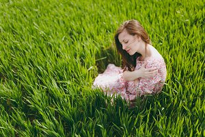 Young brunette tender beautiful woman with closed eyes in light patterned dress sitting on grass relaxing resting in sunny weather in field on bright green background. Lifestyle, leisure concept.
