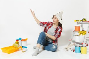 Beautiful woman in newspaper hat pointing hand aside on copy space, sit on floor with instruments for renovation apartment isolated on white background. Wallpaper, painting tools. Repair home concept.