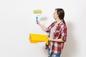Young beautiful woman holding paint tray and pointing paint roller for wall painting on copy space isolated on white background. Instruments, tools for renovation apartment room. Repair home concept.