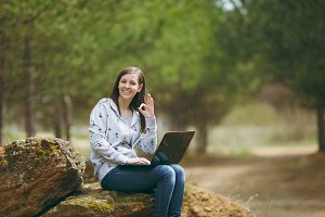 Young successful smart business woman or student in casual clothes sitting on stone using laptop and showing Ok sign in city park or forest working outdoors on green background. Mobile Office concept.