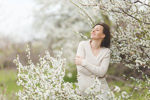 Young relaxed tender pretty woman with closed eyes in light casual clothes holding hands folded in city garden or park on blooming tree background. Spring nature, flowers. Lifestyle, leisure concept.