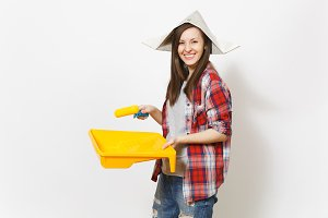 Young smiling beautiful woman in newspaper hat holding roller for wall painting and paint tray isolated on white background. Instruments, tools for renovation apartment room. Repair home concept.