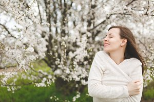 Young smiling relaxed tender beautiful woman with closed eyes in light casual clothes standing in city garden or park on blooming tree background. Spring nature, flowers. Lifestyle, leisure concept.