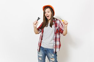 Young shocked beautiful woman in protective construction orange helmet holding toy screwdriver and wrench isolated on white background. Instruments for renovation apartment room. Repair home concept.